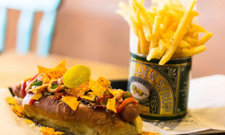 Hotdog, loaded with toppings and nachos, and a side order of fries in a syrup tin, from Hogwurst, Cardiff