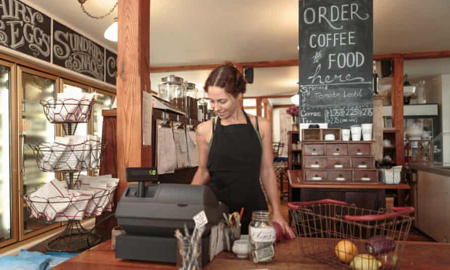 Female shop owner uses the till in a cafe