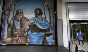 Graffiti with the ancient philosophers Plato, left, and Aristotle on the shutter of a cafe in Athens.