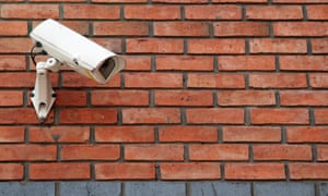 A white cctv camera mounted on a wall
