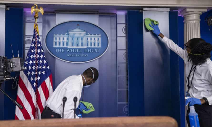 A cleaning crew wipes down a podium where Donald Trump was due to speak in the White House.