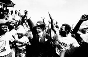 Winnie Mandela raises her fist during a funeral for 17 black people killed during fierce rioting in Johannesburg