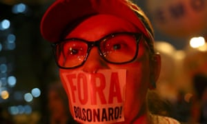 Demonstrator with 'Out, Bolsonaro' sticker taped over mouth