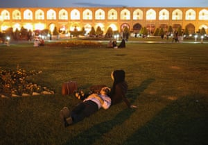 A couple lies in the Naqsh-e Jahan Square in Isfahan, surrounded by buildings from the Safavid era.