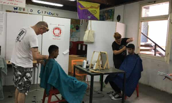 Iranian refugees get their hair cut at the Miksalište refugee centre in central Belgrade.