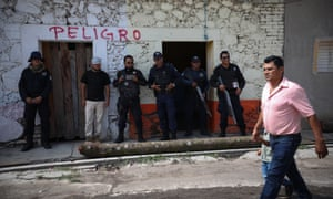 A man and child walk past security forces in the town of Tepexco, where alleged criminals were lynched this month.