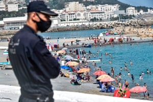 A mask-clad policeman watches as people cool off in the water at el-Kettani beach in the Bab el-Oued suburb of Algeria's capital, Algiers, on 15 August, 2020, as the country eases pandemic restrictions.