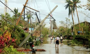 Residents walk past partially toppled electric posts after Nock-ten hit Malinao, Albay.