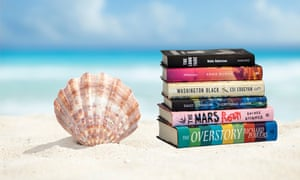 Low angle view of a scallop shell and books in the sand beach of the Caribbean sea