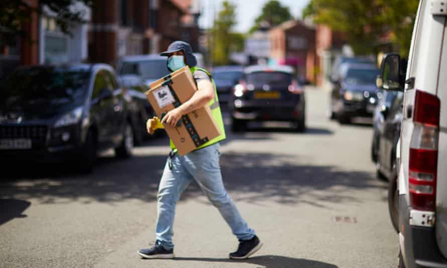 Delivery driver with mask and parcel crossing road