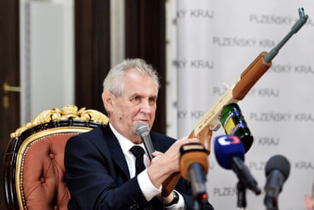 """Czech President Miloš Zeman holds a mock assault rifle with """"At journalists"""" inscribed on it in October 2017."""