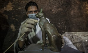 An archaeologist cleans a ancient cat statue