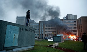 A man stands on a wall with a slogan reading: 'Police kills' next to a burning car in Bobigny riots