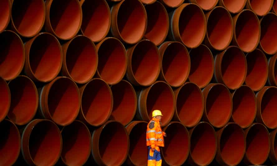 A worker walks in front of stacked pipe sections