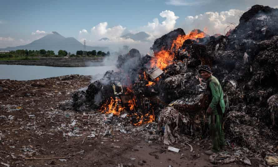 A man burns imported plastic waste at a dump in Mojokerto, in Indonesia's East Java province