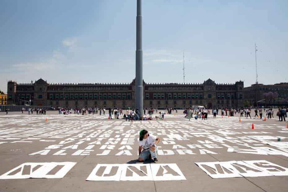 Women paint the names of victims of femicide in front of Mexico's national palace before a march on 8 March 2020.