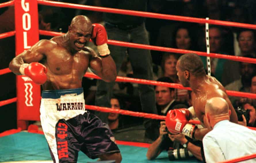 Evander Holyfield winces after having his ear bitten by Mike Tyson.