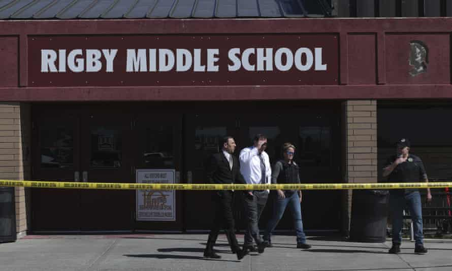Officers leave Rigby middle school in Rigby, Idaho, after a shooting on 6 May. Two students and the school custodian were shot in the incident but all three survived.