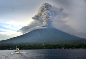 A fisherman in a traditional boat sails in front of the volcano