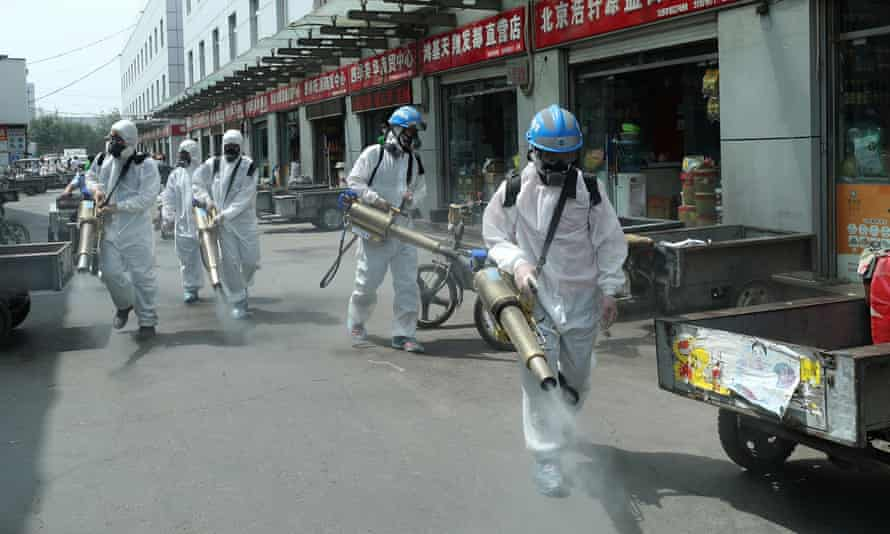 Volunteers disinfect the Yuegezhuang wholesale market in Beijing following new cases of coronavirus in the Chinese capital.