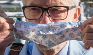 Jeremy Corbyn putting on a mask as he left his home today.
