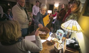 Sharon McNutt hands the ballots to the secretary to be counted at a caucus site Monday, Feb 1, 2016, in Silver City, Iowa. (AP Photo/Dave Weaver)
