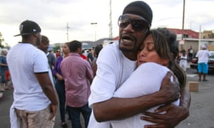 People embrace at the scene of the police shooting in El Cajon