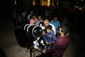 Children queue up to see the blood moon through a telescope in Ramallah, West Bank.