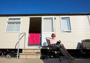 Carol Cunliffe reading outside her static caravan after spending a day paddle boarding on the Menai strait.