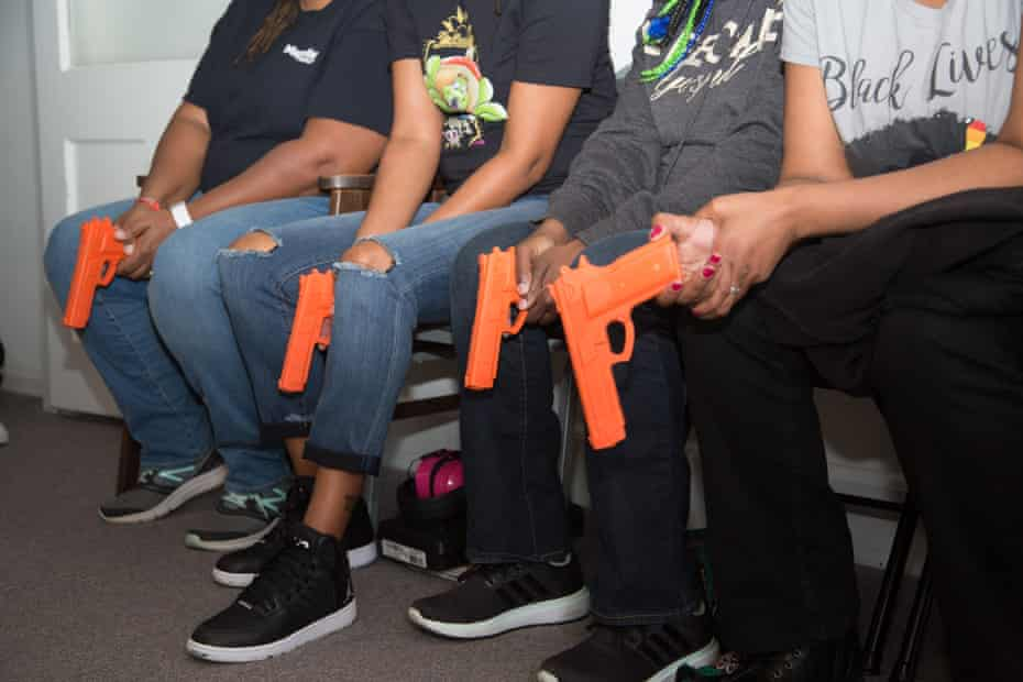 Participants hold fake guns in Marchelle Tigner's sold-out class in Lawrenceville, Georgia.