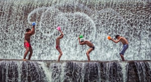 A group of children playing at the dam in Bali in the hot afternoon after school.