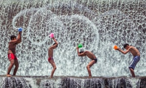Children playing at a dam in Bali in the hot afternoon after school.