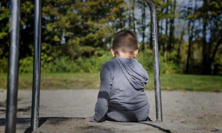 A small boy sitting alone in a playground