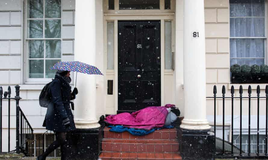 A homeless person sleeps in a doorway in London.