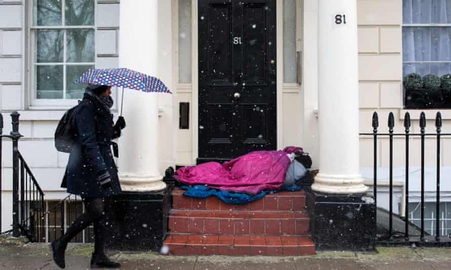 A homeless person sleeps on a doorstep in London during a snow in February this year.