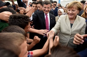 Turkey's prime minister Ahmet Davutoğlu and German Chancellor Angela Merkel greet people at a refugee camp in Gaziantep, Turkey