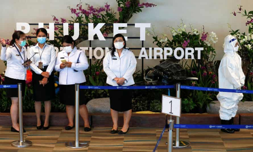 Airport officials wait while a plane carrying the first foreign tourists arrives at the airport as Phuket reopens to overseas tourists.
