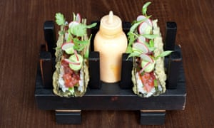 Open temaka sushi, with tuna, scallion and tobiko on a wooden slab with a plastic bottle of mayonnaise