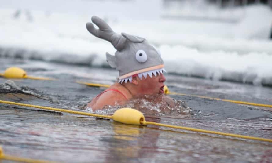 Guardian writer Sally Goble swimming in the ice pool in Skellefteå, Sweden – wearing her woolly hat, in the shape of a shark.