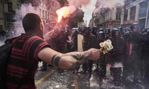 A man holds a bouquet of flowers and a torch as he faces riot police during a demonstration in Lyon, central eastern France.