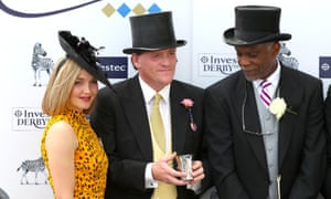 Retired cricketer Michael Holding and Victoria Pendleton present the trophy to Richard Hannon (centre) for winning after the Princess Elizabeth Stakes at Epsom.