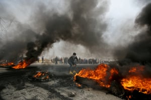 A demonstrator moves burning tyres during anti-government protests in Basra, Iraq