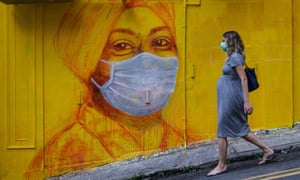A pregnant woman wearing a face mask as a precautionary measure walks past a street mural in Hong Kong
