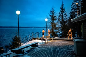"""Tampere, Finland. Longitude: 23¡ 80' 39.69"""" Bathers take a dip in Lake Näsijärvi after emerging from the Kaupinoja sauna"""