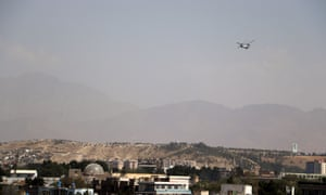 A military transport helicopter flies overhead in Kabul earlier today ready to evacuate foreigners