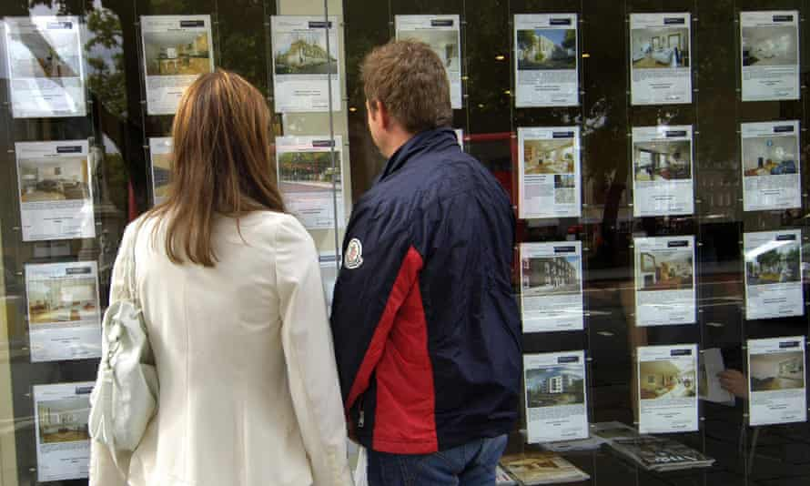 People standing outside an estate agent's window