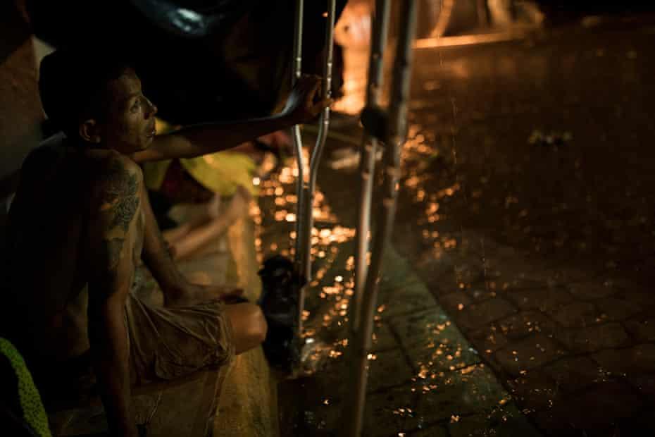 A man seeks refuge from the rain.