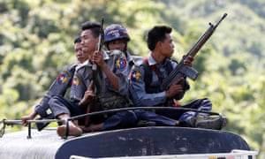 Police guard a UN convoy as they flee from Maungdaw after Arakan Rohingya Salvation Army attacks in Myanmar.