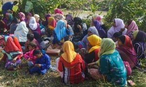 Rohingya refugees, mostly women and children, sitting on the ground, in Malaysia