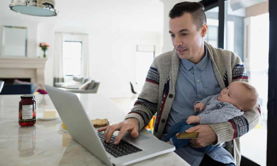 Father holding baby son and working at laptop